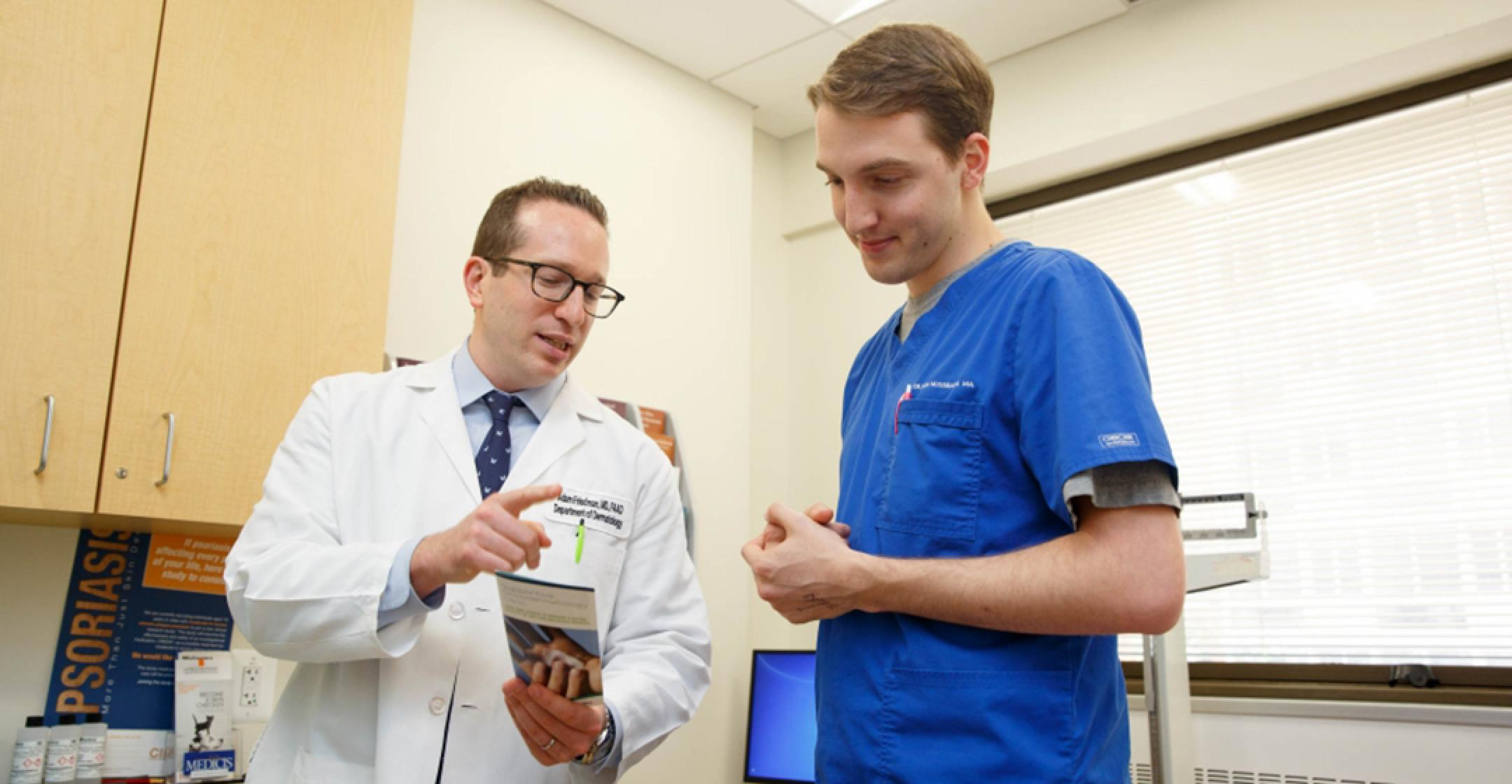 Adam Friedman with staff member Dillon Nussbaum in the Supportive Oncodermatology Clinic.