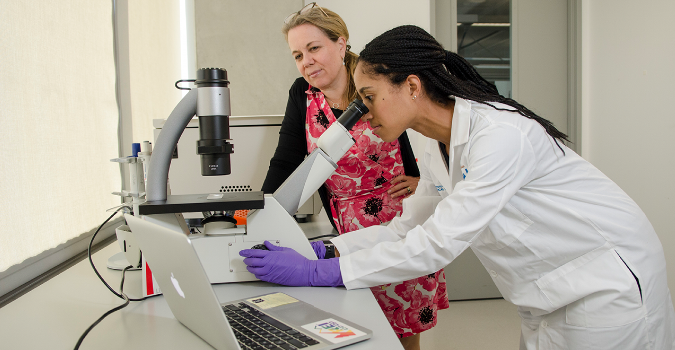 Dr. Catherine Bollard with Postdoctoral Researcher Looking Through Microscope