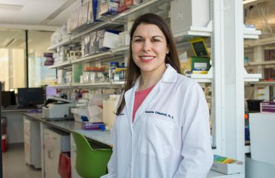 Research standing in a lab in a white coat
